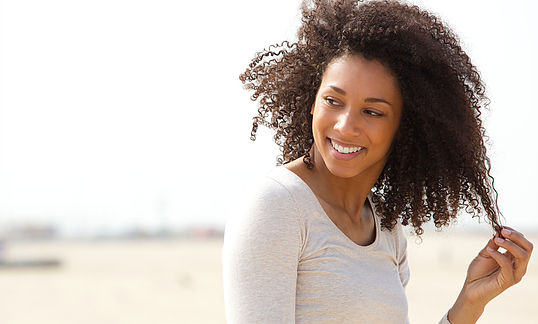 Close up portrait of a beautiful young woman smiling with curly hair
